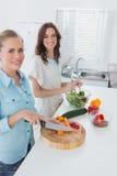 Vrouwen die samen en camera bekijken koken stock foto