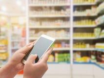 Vrouwen die slimme telefoon op apotheek met behulp van Stock Afbeeldingen