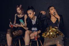 vrouwen die smartphones met bored vriend dichtbij gebruiken stock afbeeldingen