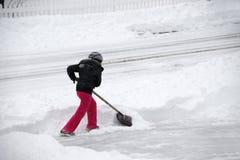 Vrouwen die sneeuw op de oprijlaan verwijderen door schop na blizzard Stock Afbeeldingen