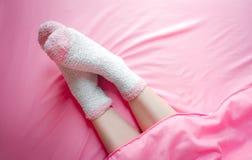 Vrouwen die sokken op de winterochtend en dekensachtergrond dragen Warm en comfortabel op beddegoedblad stock afbeelding