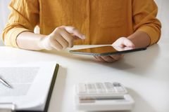 vrouwen die tablet gebruiken terwijl het werken in haar bureau stock foto's
