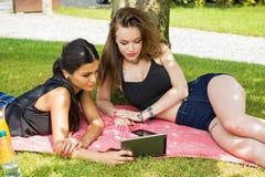Vrouwen die tablet in park gebruiken stock afbeeldingen