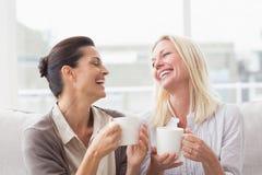 Vrouwen die terwijl het hebben van koffie in woonkamer roddelen Stock Afbeeldingen