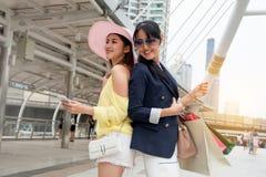 Vrouwen die van het weekend genieten die en het bekijken smartphone winkelen stock foto