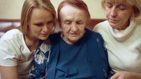 Vrouwen die van verschillende leeftijd door oude familie kijken stock videobeelden