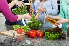 Vrouwen die voedsel voor een partij voorbereiden Stock Afbeeldingen