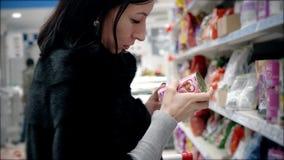 Vrouwen die voedsel voor huisdieren in supermarkt kiezen stock videobeelden