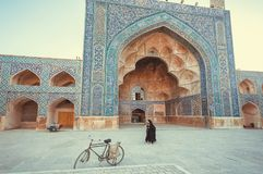 Vrouwen die voorbij een historische Perzische moskee met mooie kunstwerken lopen Stock Foto's
