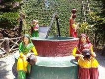 Vrouwen die water trekken van een put Stock Fotografie