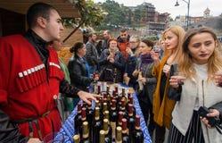 Vrouwen die wijn met barman in nationaal Georgisch kostuum proeven bij festival Royalty-vrije Stock Afbeelding