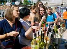 Vrouwen die witte wijn in openluchtbar proeven Royalty-vrije Stock Foto's