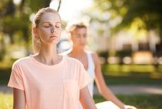 Vrouwen die yoga doen in openlucht bij zonsopgang Ochtendmeditatie stock afbeeldingen