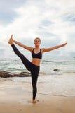 Vrouwen die yoga met de erachter oceaan doen Royalty-vrije Stock Fotografie