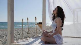 Vrouwen die yoga op dijk, diep ademmeisje die aan kustoceaan doen, vrouw op strand mediteren, stock videobeelden