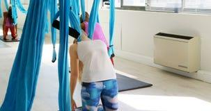 Vrouwen die yoga op hangmat 4k doen stock video