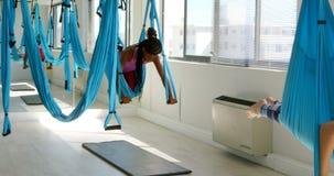 Vrouwen die yoga op hangmat 4k doen stock footage