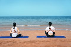 Vrouwen die Yoga op het strand doen royalty-vrije stock foto's