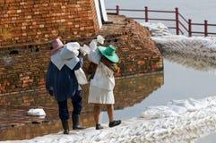 Vrouwen die zandzakken dragen tijdens vloed in Thailand royalty-vrije stock fotografie
