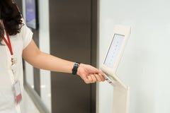 Vrouwen die zeer belangrijk kaarttoegangsbeheer houden om liftvloer te openen en de vloer te kiezen Royalty-vrije Stock Afbeeldingen