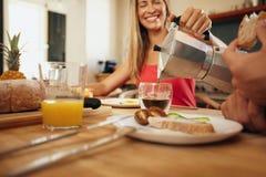 Vrouwen dienend ontbijt aan de mens in keuken Stock Fotografie