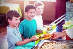 Vrouwen dienend voedsel aan glimlachende schoolkinderen royalty-vrije stock fotografie
