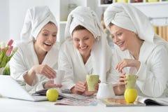 Vrouwen dragen witte badjassen met laptop Stock Afbeelding