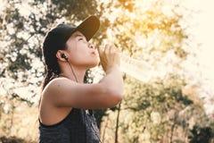 Vrouwen drinkwater op boomachtergrond royalty-vrije stock afbeelding