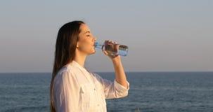 Vrouwen drinkwater van een fles op het strand stock videobeelden