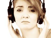 Vrouwen droevig meisje in grote hoofdtelefoons het luisteren muziek Royalty-vrije Stock Afbeelding