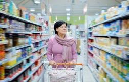 Vrouwen duwend boodschappenwagentje die goederen in supermarkt bekijken Stock Afbeelding