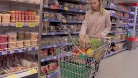 Vrouwen duwend boodschappenwagentje in kruidenierswinkelopslag stock videobeelden