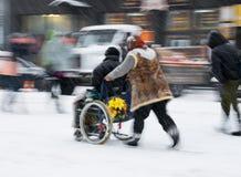Vrouwen duwende man in een rolstoel Stock Afbeelding