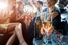 Vrouwen en mannen die met dranken in een limousineauto vieren stock foto
