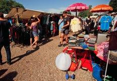 Vrouwen en mannen die op goederen in de stapels van tweede hand letten Stock Foto's