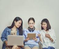 Vrouwen en vrienden het gebruiken van telefoon en computer stock afbeeldingen