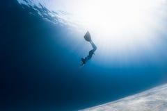 Vrouwen freediver glijdende bewegingen over zandige bodem stock foto