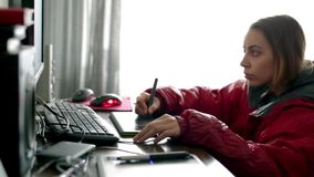 Vrouwen freelance ontwerper die, in benedenparka dragen thuis werken die stock videobeelden