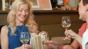 Vrouwen geven huidig aan vriend bij wijnbar stock video