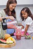Vrouwen gietend fruit van een mixer stock foto's