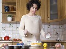 Vrouwen gietende suiker in het deeg voor cupcakes Stock Afbeeldingen