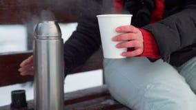 Vrouwen gietende thee van een thermosfles in een mok stock footage