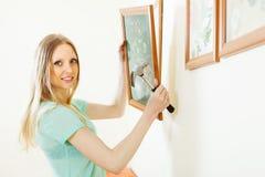 Vrouwen hangend beeld met bloemen op muur thuis Stock Afbeelding