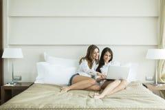 Vrouwen in het bed met laptop Stock Afbeeldingen