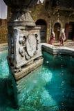 Vrouwen in historische uitrusting die door middeleeuwse fontein in Ascia overgaan royalty-vrije stock afbeelding