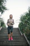 Vrouwen jogger leeglopende stappen die aan muziek luisteren Stock Foto's