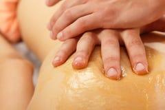 Vrouwen jonge krijgende massage met honing Stock Afbeeldingen