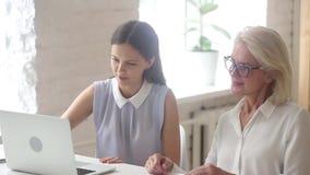 Vrouwen jonge werknemer die aan bejaarde collega met online programma helpen stock videobeelden