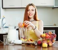 Vrouwen kokende dranken met mixer van perziken royalty-vrije stock foto's