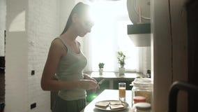 Vrouwen Kokende Toost met Boter voor Ontbijt op Moderne Keuken stock videobeelden